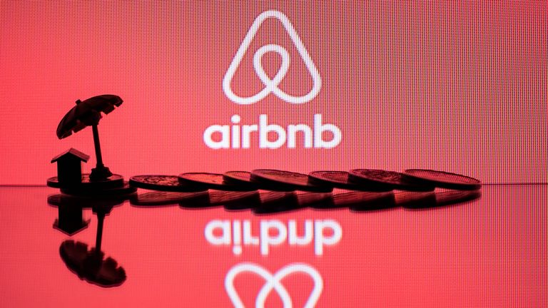 This illustration picture taken in Paris on August 29, 2018, a toy umbella and coins  next to the logo of  rental website Airbnb. (Photo by JOEL SAGET / AFP)        (Photo credit should read JOEL SAGET/AFP/Getty Images)