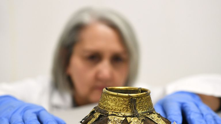 Conservator Claire Reed inspecting the remains of a wooden drinking vessel with a decorated gold neck