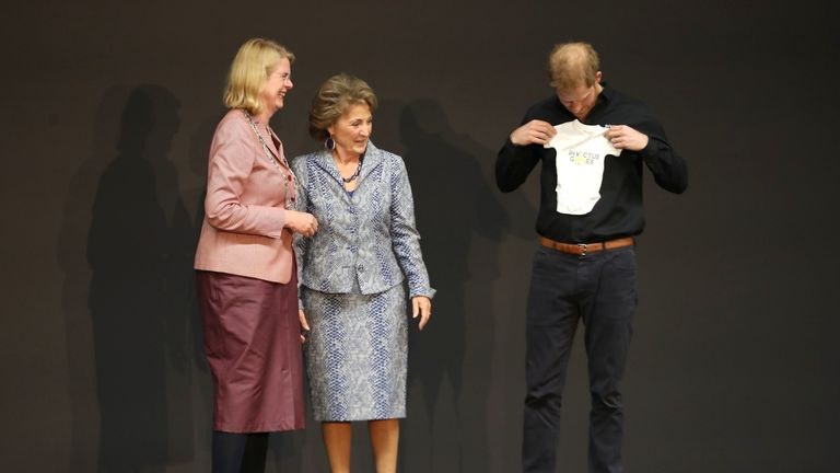 Harry accepts a gift of an Invictus baby gro for Archie