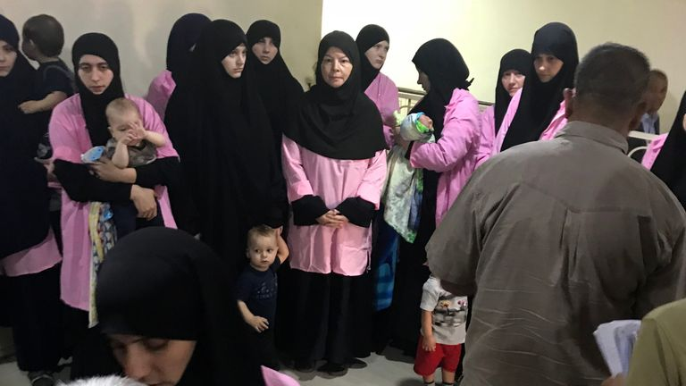 A picture taken on April 29, 2018 in the Iraqi capital Baghdad's Central Criminal Court shows Russian women who have been sentenced to life in prison on grounds of joining the Islamic State (IS) group standing with children in a hallway