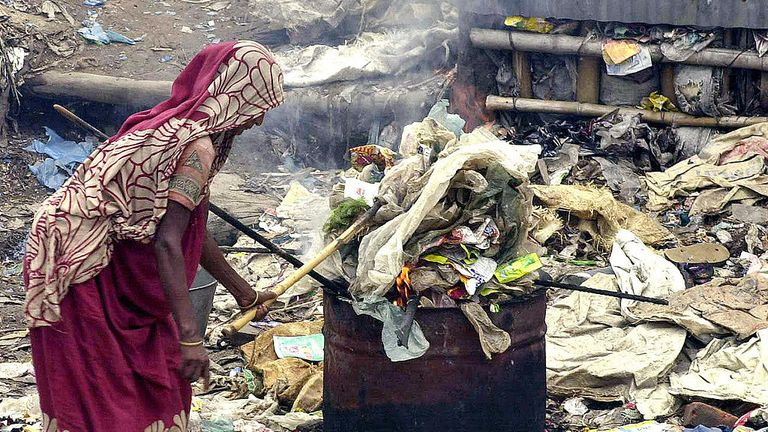 DHAKA, BANGLADESH: A Female Bangladeshi labourer burns rubbish as she works in a plastic re-cycling factory in the Rasulpur District of Dhaka, 15 September 2005.