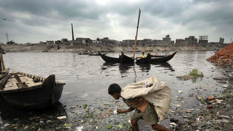 A Bangladeshi child collects garbage from the litter-strewn river bank in Dhaka