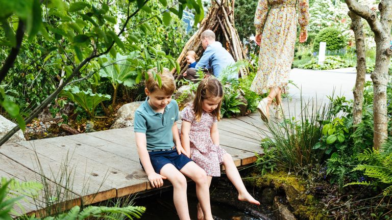 George and Charlotte dip their toes in the pond in the garden designed by their mother