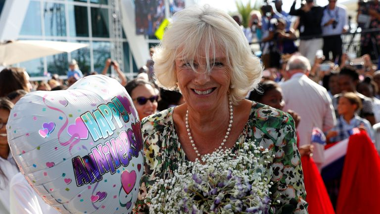 Camilla is given a balloon and flowers for their anniversary