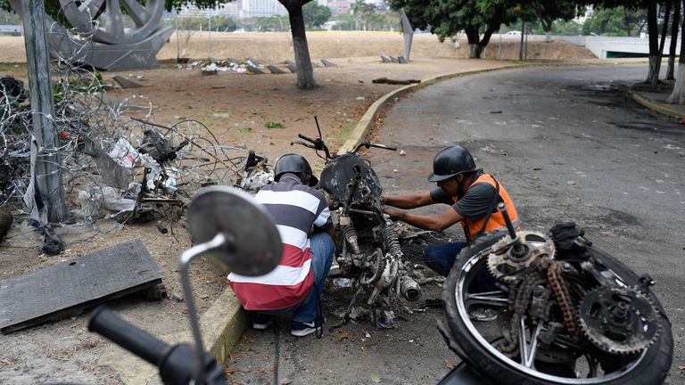 Two men dismantle a burned motorcycle to recycle its parts at Luis Roche Avenue in Caracas