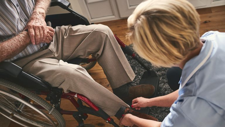 Healthcare worker tie shoe laces of disabled senior man