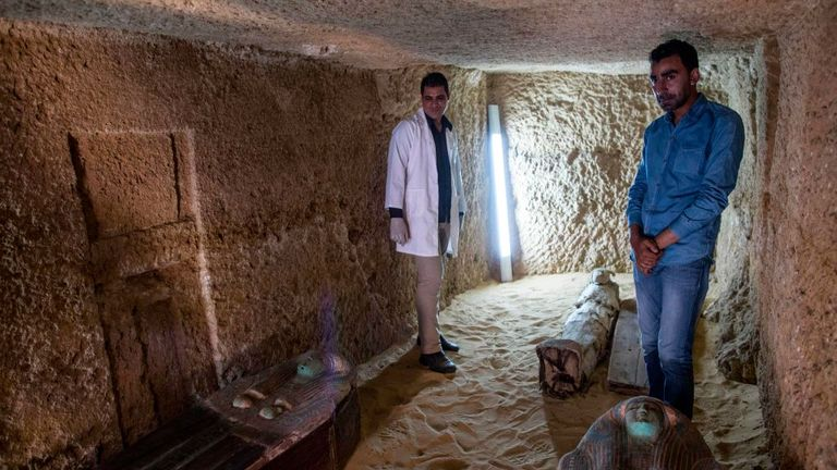 Excavation workers stand next to sarcophagi inside a burial shaft at the Giza pyramid plateau, on the southwestern outskirts of the Egyptian capital Cairo, on May 4, 2019, following the discovery of several Old Kingdom tombs and burial shafts. (Photo by MAHMOUD KHALED / AFP) (Photo credit should read MAHMOUD KHALED/AFP/Getty Images)