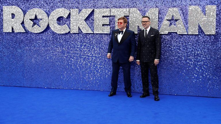 Elton John (left) arrived at the premiere with his husband David Furnish (right) on the back of a glittery golf buggy