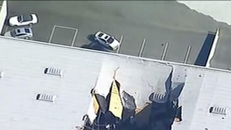 The hole left in the roof of a warehouse in California after an F-16 fighter jet crashed through it