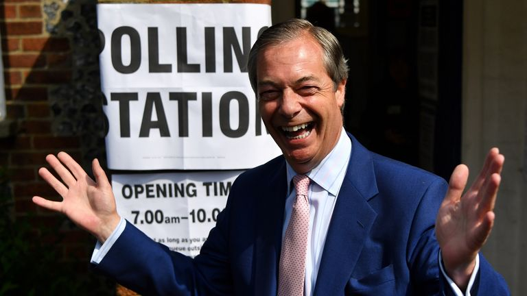 Brexit Party leader Nigel Farage gestures as he arrives at a polling station