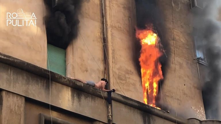 A man in Rome evades fire by hanging on to a ledge.