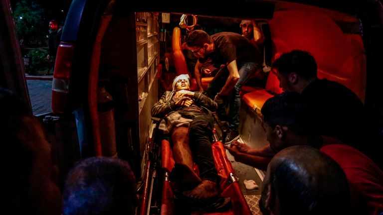 A wounded Palestinian man is loaded into an ambulance