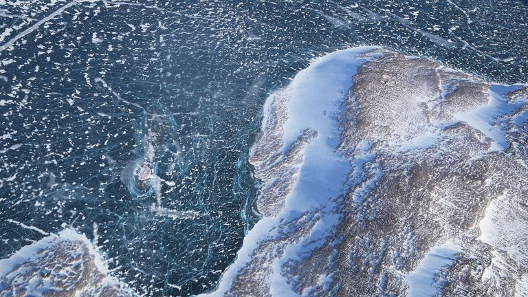 Sea ice (TOP) meets land as seen from NASA's Operation IceBridge research aircraft along the Upper Baffin Bay coast on March 27, 2017 above Greenland. Greenland's ice sheet is retreating due to warming temperatures.