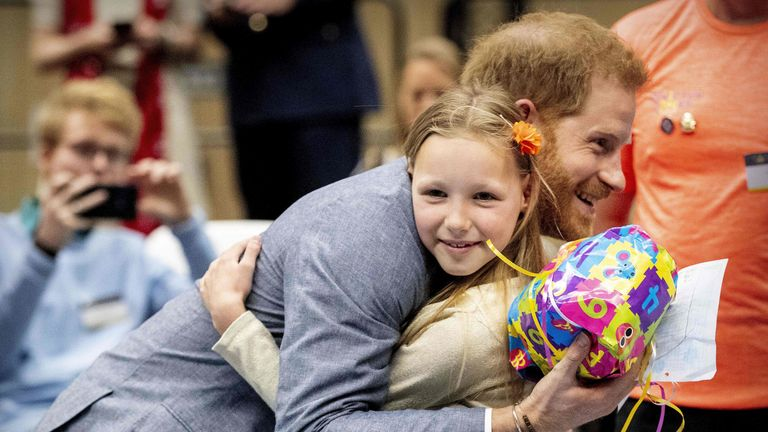 Harry hugs a young admirer after getting a gift