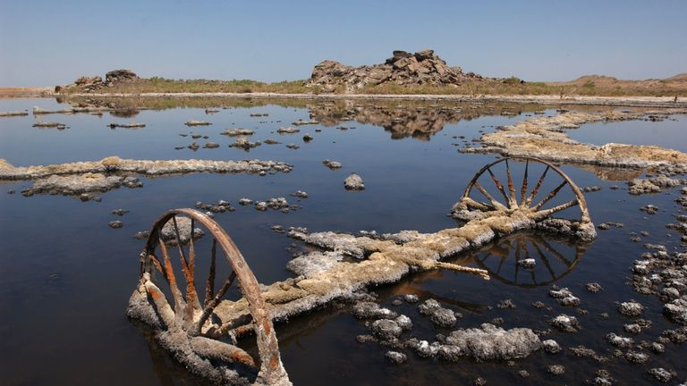 SALTON SEA, CA - JUNE 17: The wheels of an old farm machine lie rusting in the field of a farm that is encrusted with salt crystals and flooded with brine from the Salton Sea, which continually rises as a result of irrigation runoff, June 17, 2003 in the Colorado Desert of southern California. The Salton Sea Authority is considering a plan to shrink the salty 376-square-mile lake, by capturing and desalting agricultural runoff that flows into the sea from Imperial Valley farms, in an effort to r