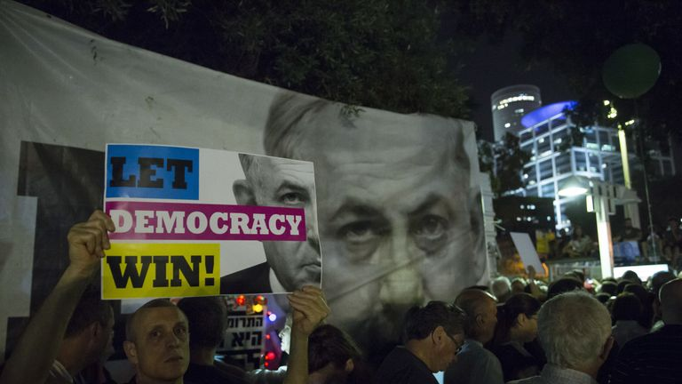 An Israeli man hold a sign at a protest against Netanyahu's 'Immunity Law'  on May 25, 2019 in Tel Aviv, Israel