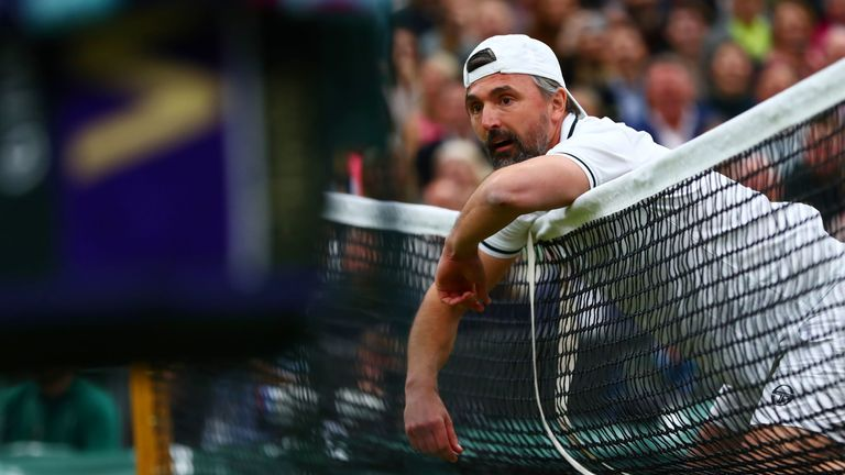 Goran Ivanisevic collapses on the net during his men's doubles match