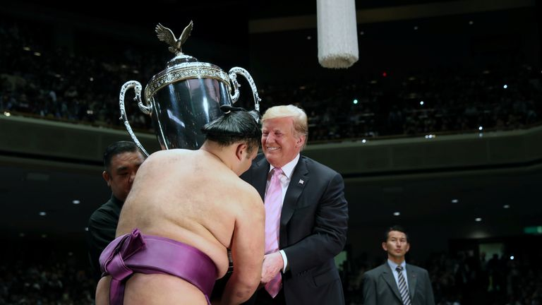 U.S. President Donald Trump presents the President's Cup to wrestler Asanoyama, the winner of the Summer Grand Sumo Tournament at Ryogoku Kokigikan Sumo Hall in Tokyo, Japan May 26, 2019