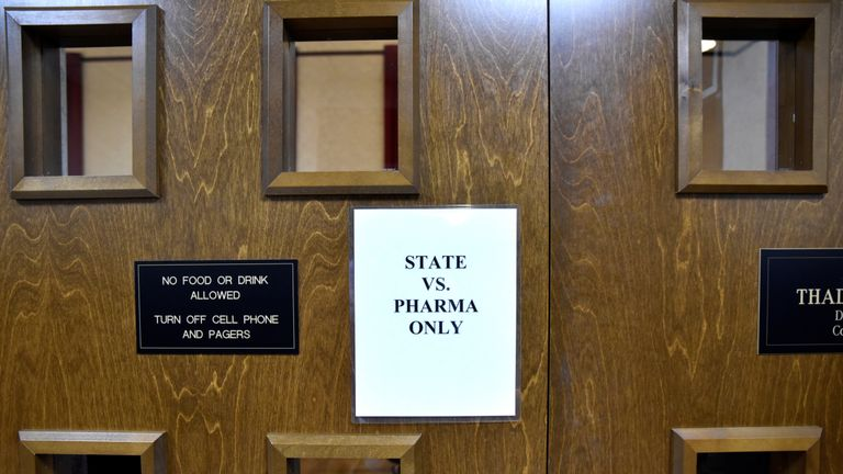 A sign is seen on the outside of the courtroom on the first day of a trial of Johnson & Johnson and Teva Pharmaceutical Industries over claims they engaged in deceptive marketing that contributed to the national opioid epidemic in Norman, Oklahoma, U.S. May 28, 2019