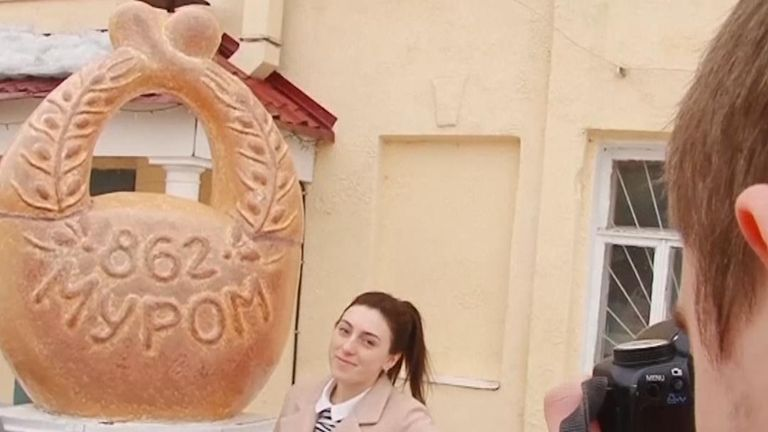 Tourists in Murom, Russia, have pictures taken next to a giant kalach roll statue