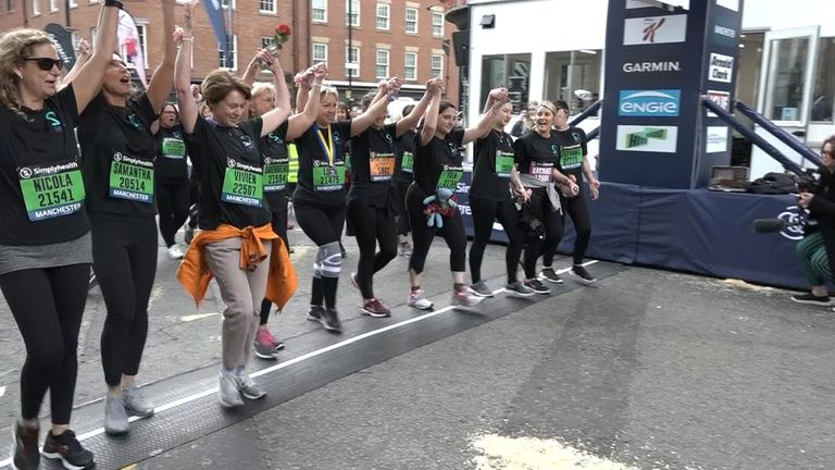 Lisa and her team hold hands as they cross the finish line