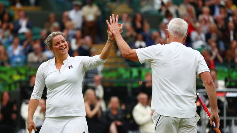 John McEnroe and his partner Kim Clijsters celebrate a point during the mixed doubles match