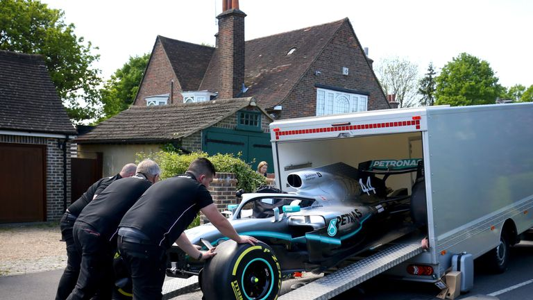 Members of the Mercedes Formula One team deliver a replica of Lewis Hamilton's Formula 1 car