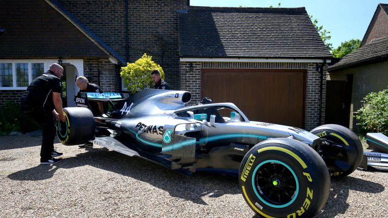 Members of the Mercedes Formula One team delivering the car