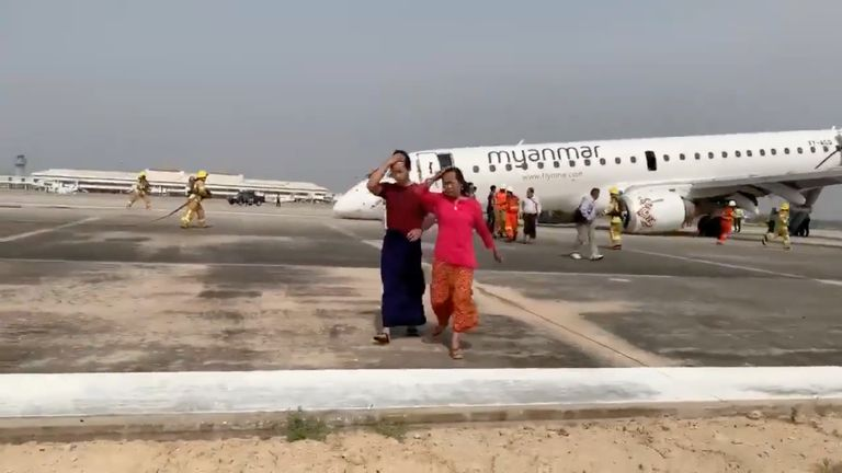 Passengers walk away from the plane after Myanmar National Airlines flight UB103 landed without a front wheel at Mandalay International Airport in Tada-u, Myanmar May 12, 2019 in this still image taken from social media video. Nay Min via REUTERS