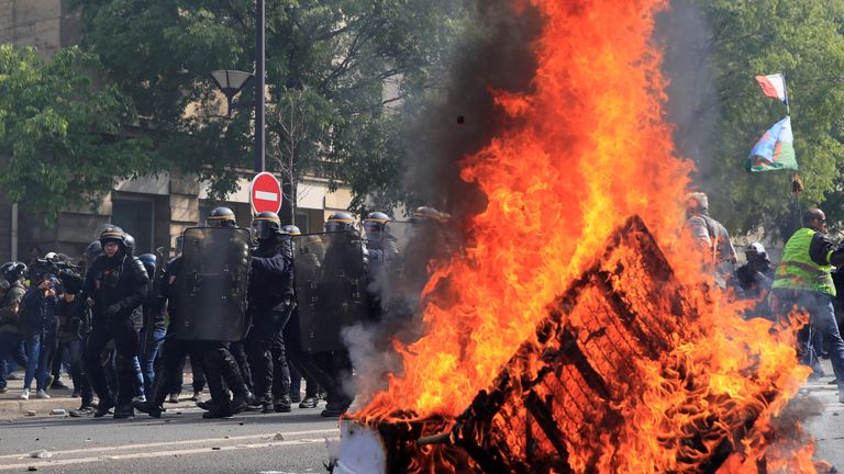 French CRS riot police stand guard next to a fire during clashes as part of the traditional May Day labour union march