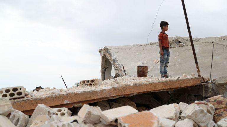 A Syrian boy stands above the rubble of a building in the village of Rabaa Jour in the the jihadist-held Syrian province of Idlib on May 6, 2019 following reported shelling and air strikes in the area