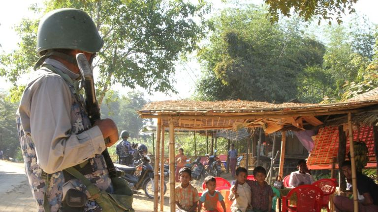 A Myanmar border guard watches over a group of Rohingya in a village in Rakhine