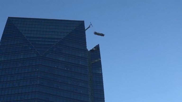 The two were stranded outside the 50-floor Devon Tower in Oklahoma City and were pulled to safety in under an hour.