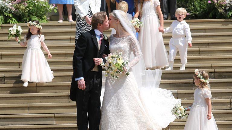 Newlyweds share a kiss on the steps of the chapel