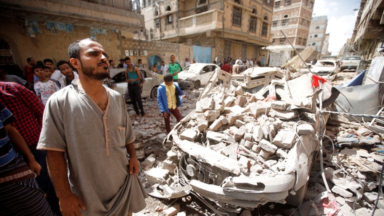 People gather at the site of an air strike launched by the Saudi-led coalition in Sanaa, Yemen on Thursday