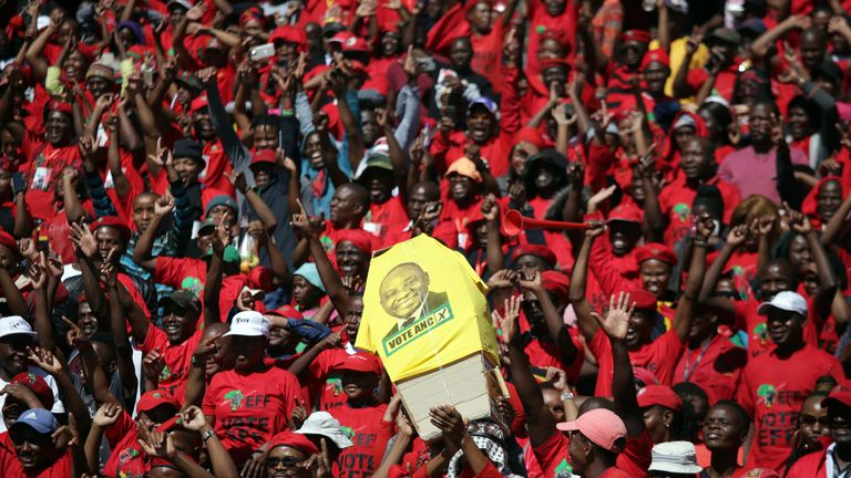 Supporters of the opposition party Economic Freedom Fighters hold a mock coffin bearing the face of the ruling president