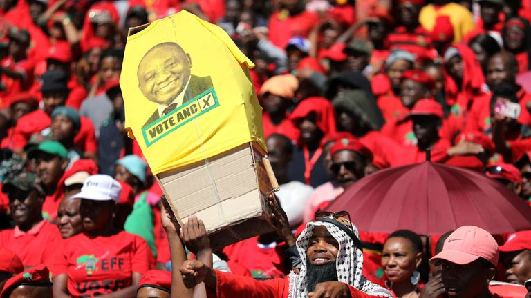 Supporters of Economic Freedom Fighters carry a mock coffin of Mr Ramaphosa