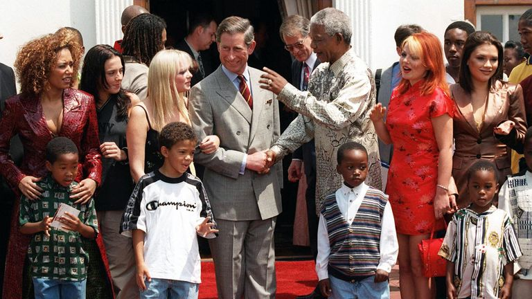 Nelson Mandela (centre right) shakes hand with Prince Charles flanked by members of the British pop group Spice Girls at his residence in Pretoria, 01 November. Prince Charles is on a week-long visit to Southern Africa and the Spice Girls will play at the Nations trust concert tonight. The Prince of Wales and his son Prince Harry will attend the performance. (Photo by Odd ANDERSEN / AFP) (Photo credit should read ODD ANDERSEN/AFP/Getty Images)