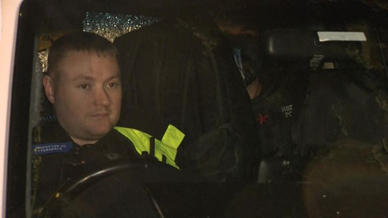 The suspect, pictured in the back of a police car with a black rucksack in front of his face, is taken into custody