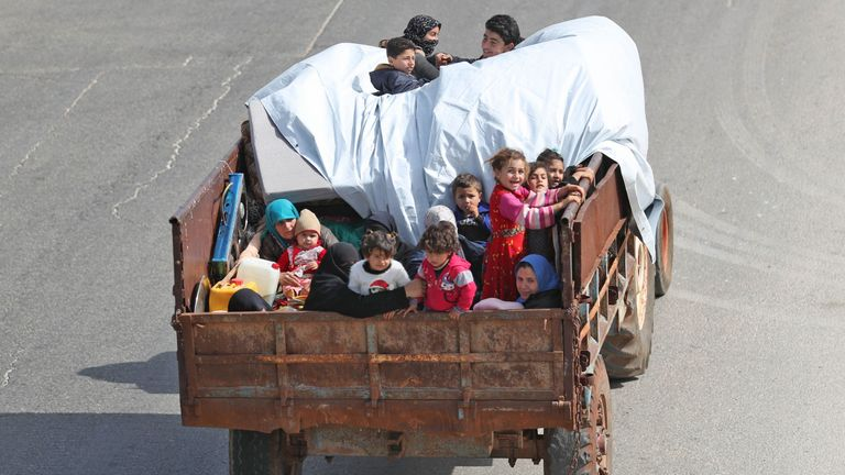 A Syrian family, riding on the back of a truck, flee from reported regime shelling on the southern countryside of the rebel-held Idlib province on May 6, 2019