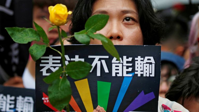 A same-sex marriage supporter holds rose to mourn those who committed suicide due to discrimination during a parliament vote on three draft bills of a same-sex marriage law, outside the Legislative Yuan in Taipei, Taiwan May 17, 2019.