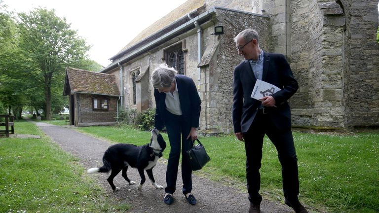 Theresa May leaves with her husband Philip following a church service