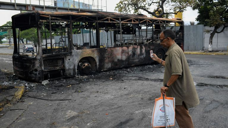 A man takes photos of a burned bus in Caracas