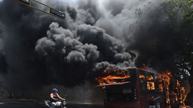 A bus was set on fire as clashes broke out in the Venezuelan capital