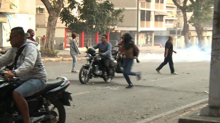 People flee after security attempt to drive them from the streets in Caracas