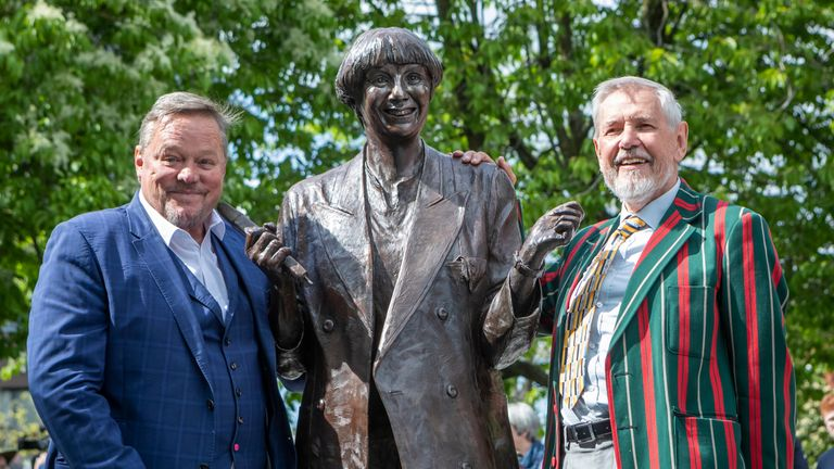 A life-size bronze statue of the late comedian, writer and actor, Victoria Wood is unveiled in Bury town centre by comedian Ted Robbins (left) and her brother Chris Foote Wood