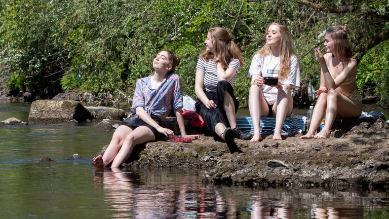 Students enjoy the sunshine alongside the River Kelvin in Glasgow