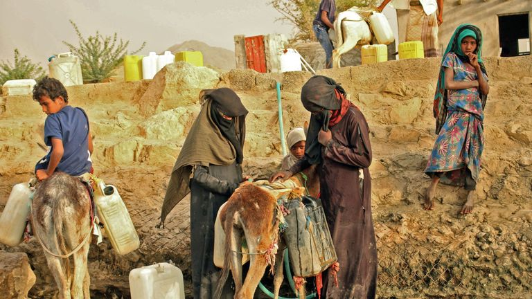 Displaced Yemenis from Hodeida fill water containers at a make-shift camp