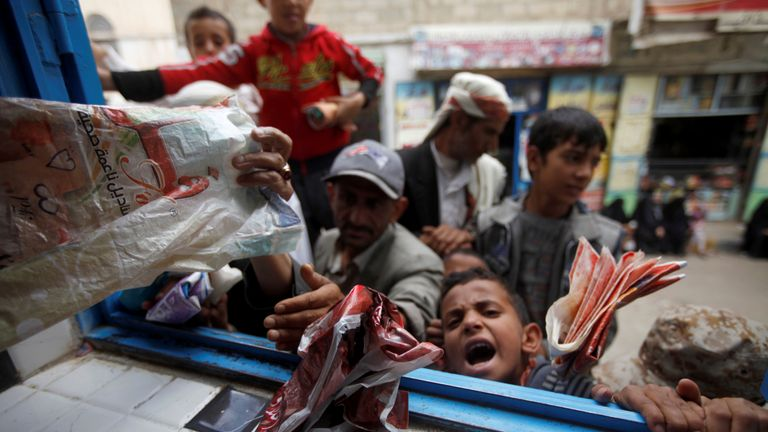 Boys waiting in line to get bread from a charitable bakery in Sanaa, the capital of Yemen