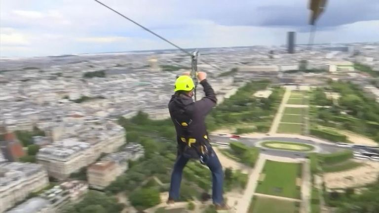 Volunteers ride a zip wire from the Eiffel Tower.